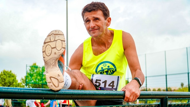 older male athlete stretching his leg prior to an outdoor sporting event - basically me, Uri Frazier, 'bout to kick some booty as I get back on the Web Developer Path